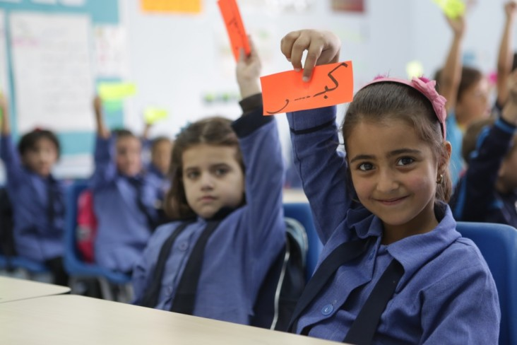 """A schoolgirl holds up a paper that says """"big"""" in Arabic."""