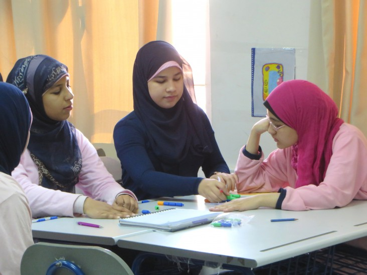 Students from the USAID-supported Maadi STEM High School for Girls experiment in class.