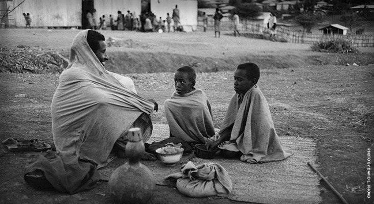 Image of an Ethiopian father and his sons at USAID food distribution in 1980s