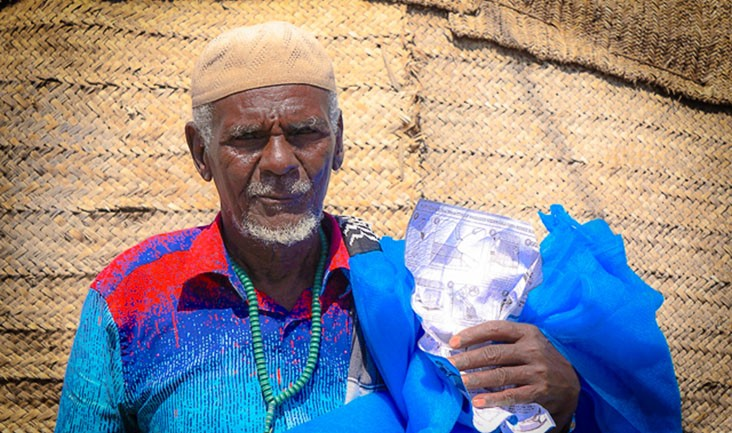 Image of Ethiopian man holding mosquito bed net
