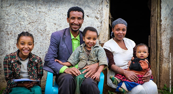 Image of a family who helps their daughters learn to read under USAID programs.