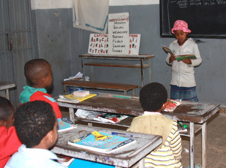 "Birhane Primary School summer reading camp student Selam Tamene reads a ""Tsehai Loves Learning"" storybook to her classmates."