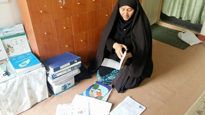 Photo of Afghanistan community health worker Fatima Khadem sorting TB records and reports. Photo credit: Nazir Ahmad Rahmani, Challenge TB
