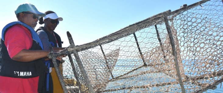 Game warden Venis Bryan and co-captain Cavin Lattibeaudiere remove an illegal fish trap from the Bluefields sanctuary.