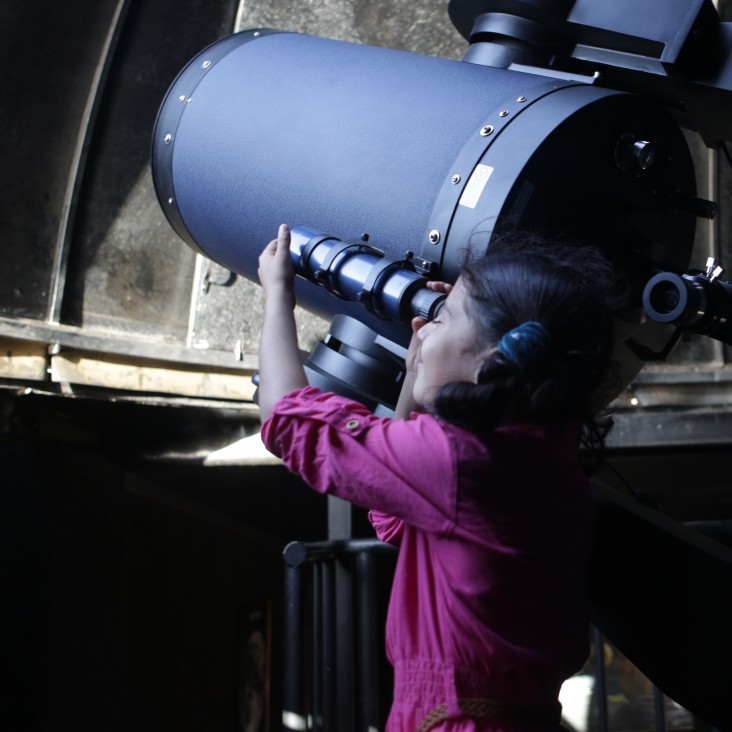A young girl looks through a telescope