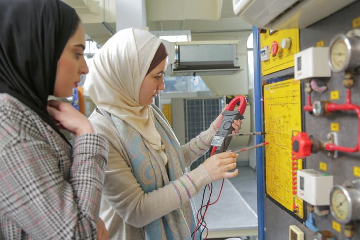 Two women stand in front a machine, looking at an electrical meter.