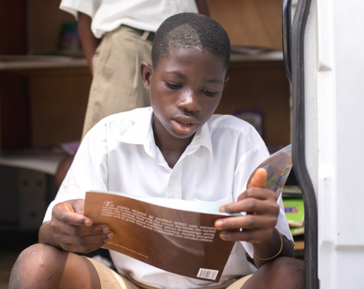 A pupil sits at the edge of a mobile library van in Ho while engrossed in a book he picked from the shelf.