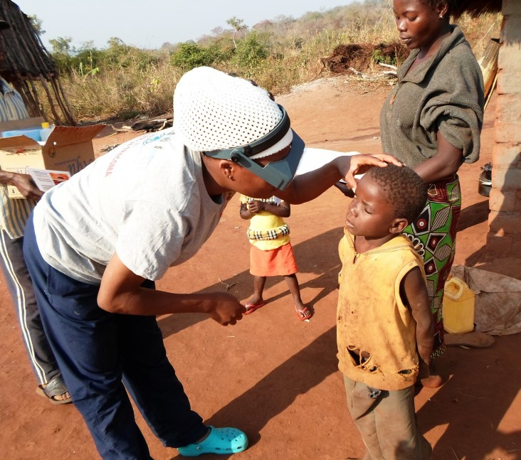 A field officer examines a child for trachoma.