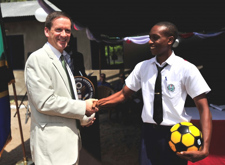 Ambassador Mark Green presents a student with a soccer ball during a dedication ceremony at Jitegemee Secondary School in Dar es Salam, Tanzania.