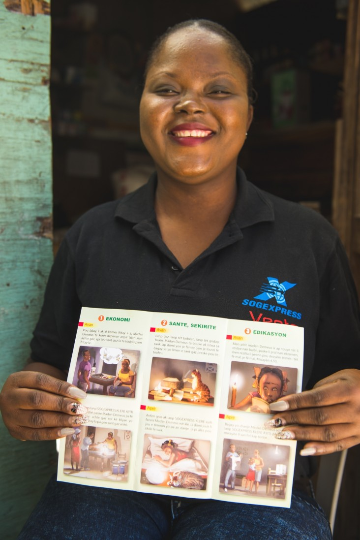 Chery Canel Chedlande, a Sogexpress sales representative, displays a brochure explaining the benefits of solar lamps.