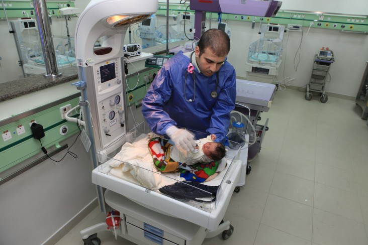 A healthcare worker treats a baby in a hospital room.