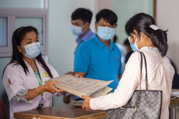 Communities have campaigned for multi-month dispensing (MMD) of HIV treatment, organized home deliveries of medicines and provided financial assistance, food and shelter to at-risk groups. Pictured, Em Ra is receiving her medical file before discussing MMD of antiretroviral medicine in Phnom Penh, Cambodia, November 2020.