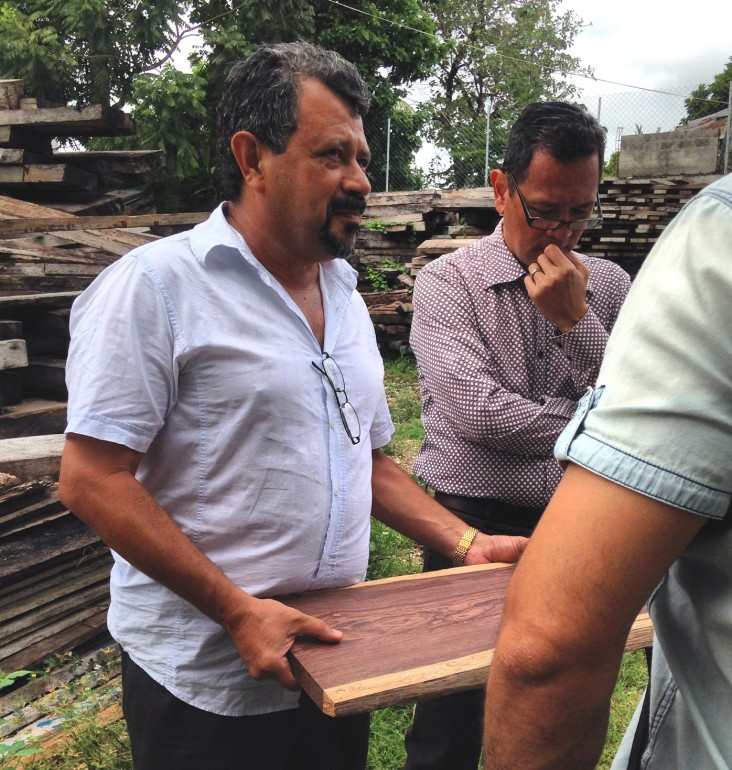 Alvaro Fernandino of USAID's Security and Justice Sector Reform Project, in glasses, examines trafficked rosewood