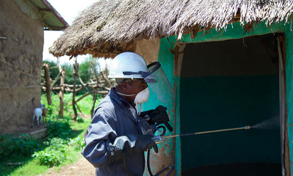 A person wearing protective gear enters a hut