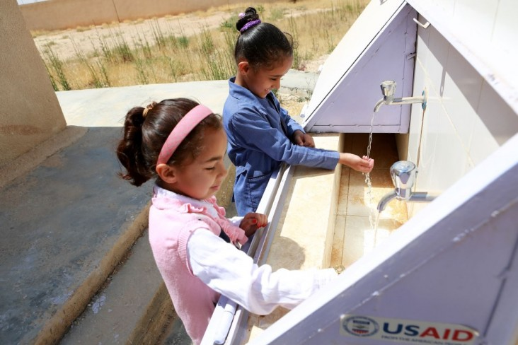 Two girls wash their hands at a USAID-branded school washbasin.