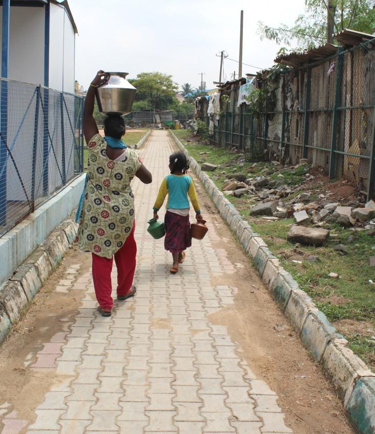 A girl and her mother return home with purified drinking water in Bengaluru's Lingarajpuram slum.