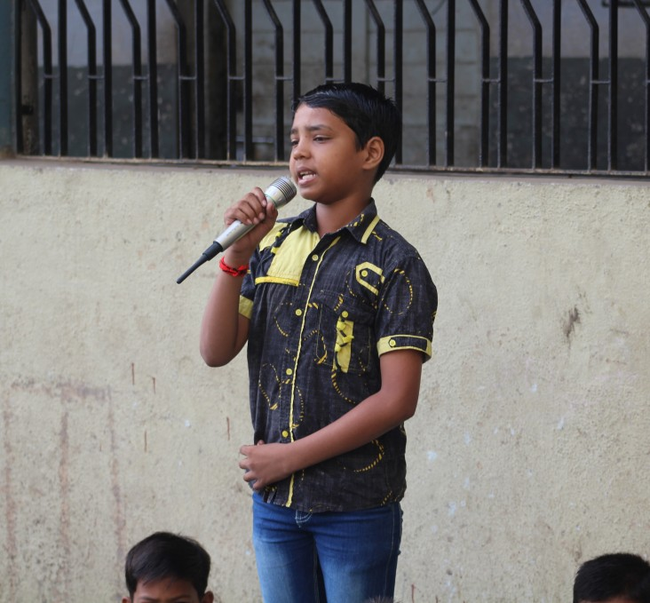 A student performs a song during the morning assembly at Kavi Kalidas Primary School.