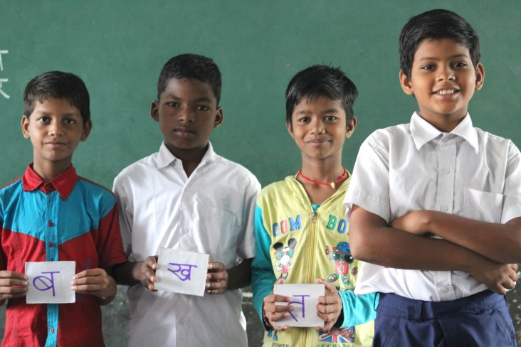 "Raj Kumar's students hold flash cards forming the Hindi word for ""time."""