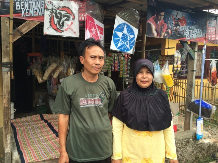 Nurita and her husband stand in front of their business in Indonesia's Banten province.