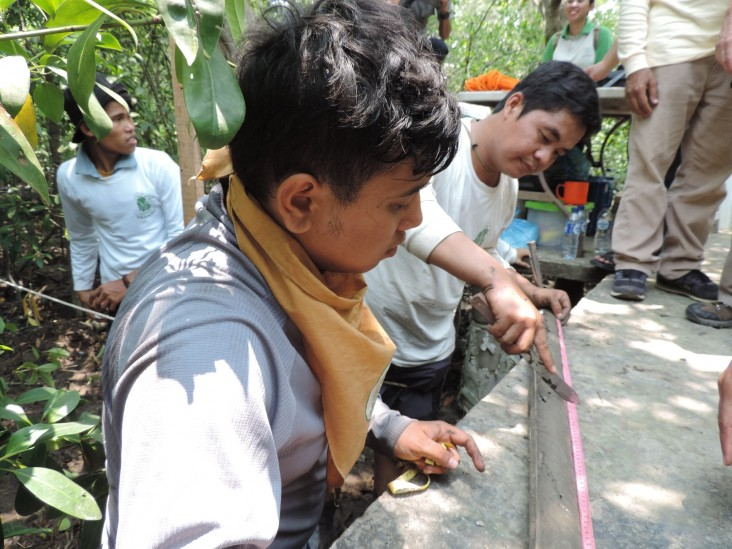 A USAID Yagasu carbon biodiversity research unit measures soil carbon content from an open-face auger in Indonesia.