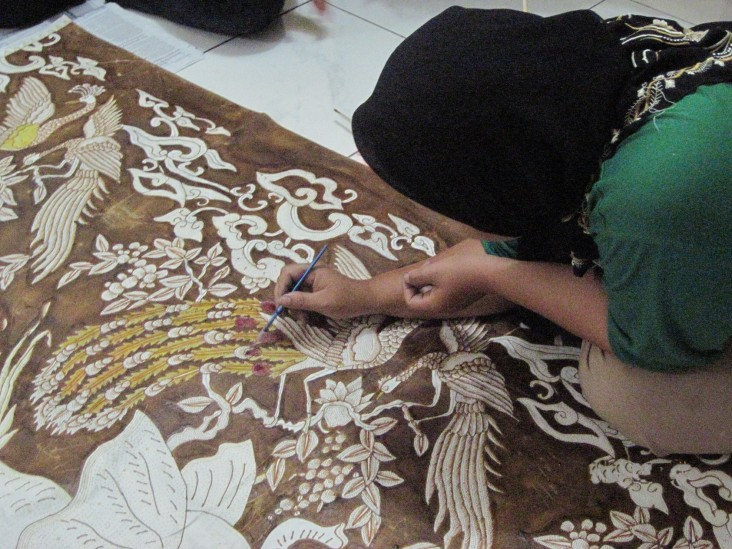 Hamidah paints on batik fabric using a natural dye derived from mangroves.