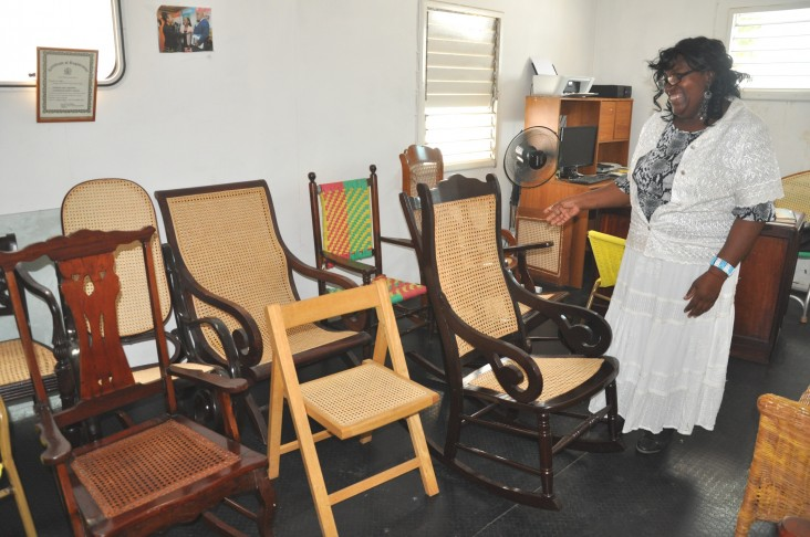 Claudette Thompson shows off the finished chairs that were caned by her team members.
