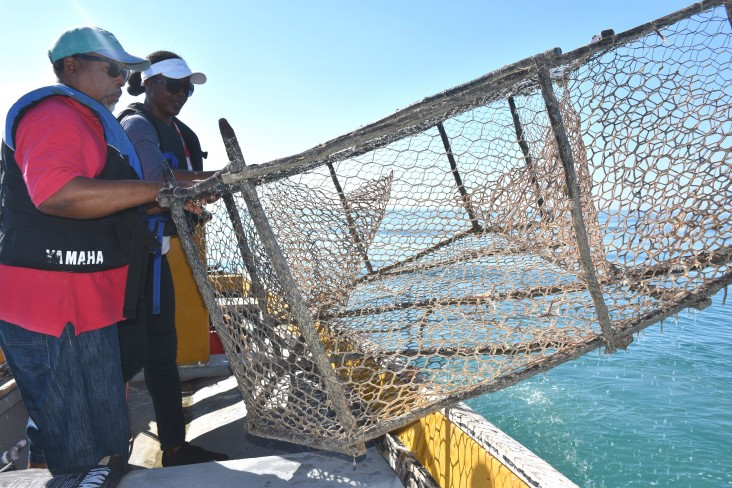 Game warden Venis Bryan, right, and co-captain Cavin Lattibeaudiere remove an illegal fish trap from the fish sanctuary.
