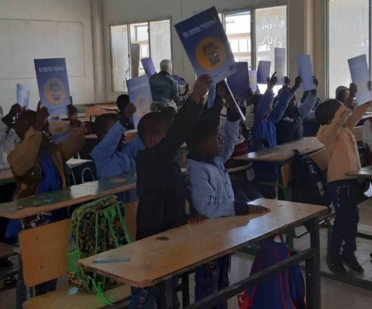 Students at a school im Murzog celebrate the arrival of their textbooks and workbooks in December, 2019.