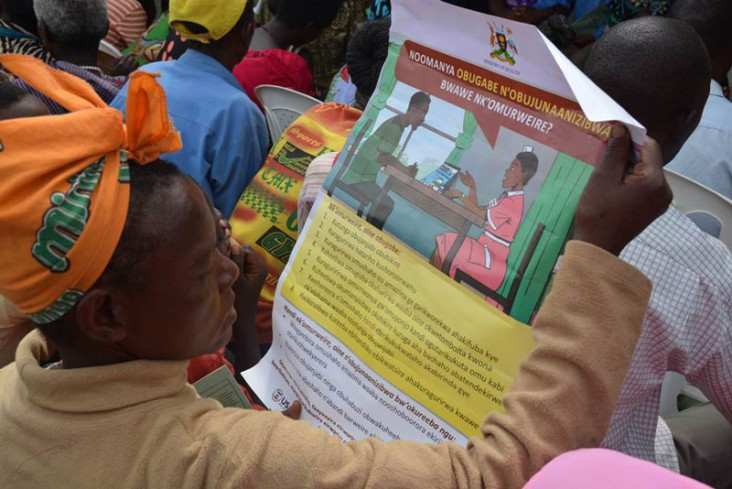 AA woman reads the local language version of the Patient's Charter at a medical camp in Bushenyi, Uganda supported by the USAID-