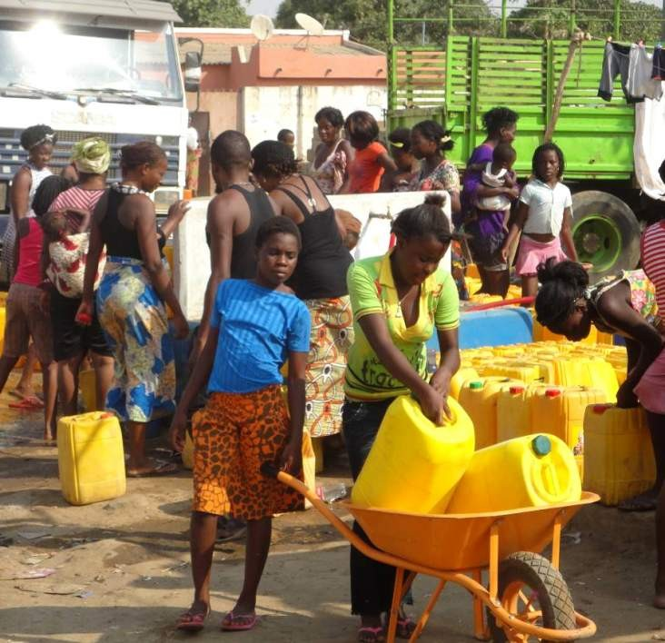 Angolan girls collect water from a USAID-funded water point in Cazenga, Luanda Province