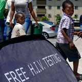 A child walking in front of a sign saying Free HIV Testing