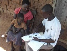 ECD Peer Educator Tonny Anyang of Apua Parish teaches a mother about baby cues.