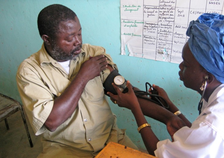 Malian community health worker trained by USAID checking blood pressure