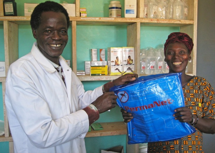Malian health worker hands over a mosquito net