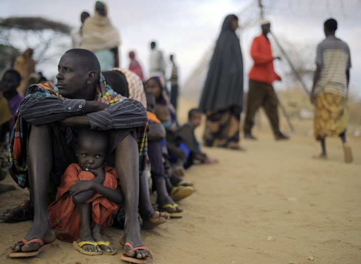 Somali refugee father and daughter sit in line at Dadaab refugee camp in Kenya