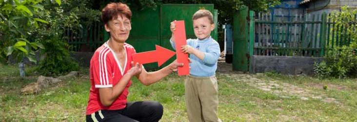 Photo of a mother and son holding a red TB arrow.