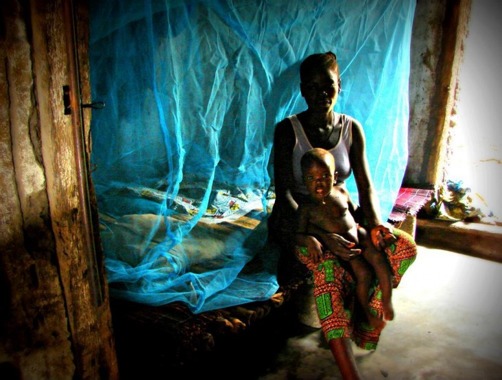 A mother and child have set up a new mosquito net in their home as a result of the 2011 bed net mass distribution campaign in Be