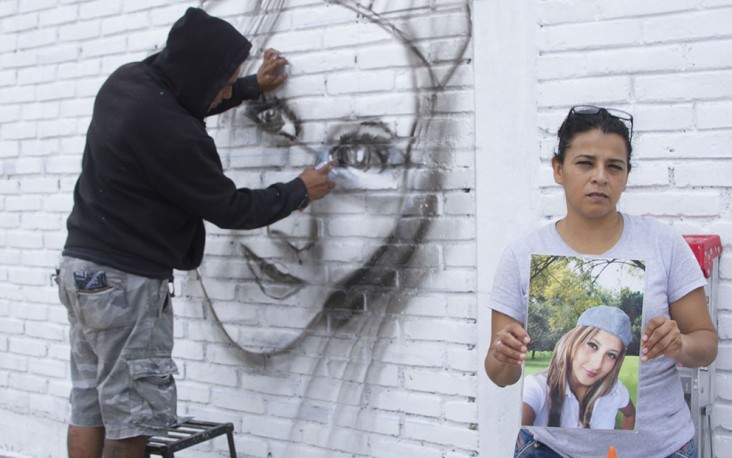 Mural painting of a disappeared woman with her mother showing her picture.