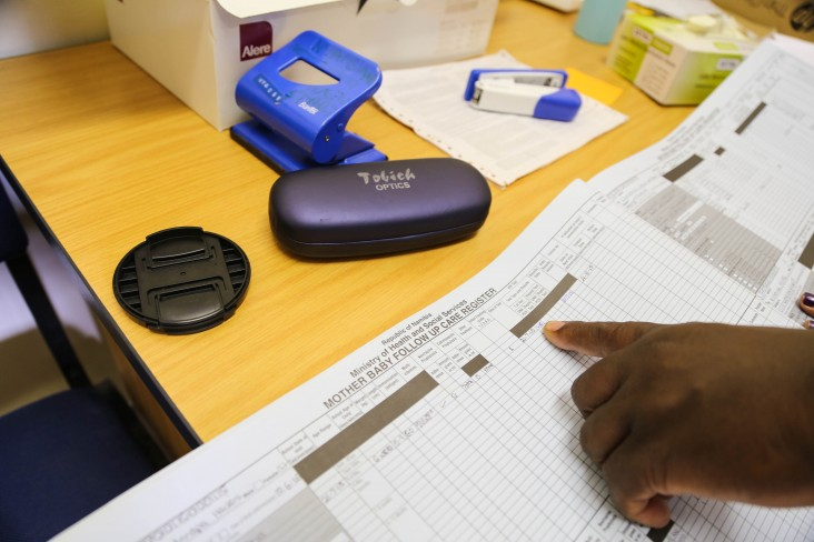 Rightwell Zulu and his team use registers at Nyangana District Hospital to track HIV status for mothers and babies, and to track follow-up visit dates.