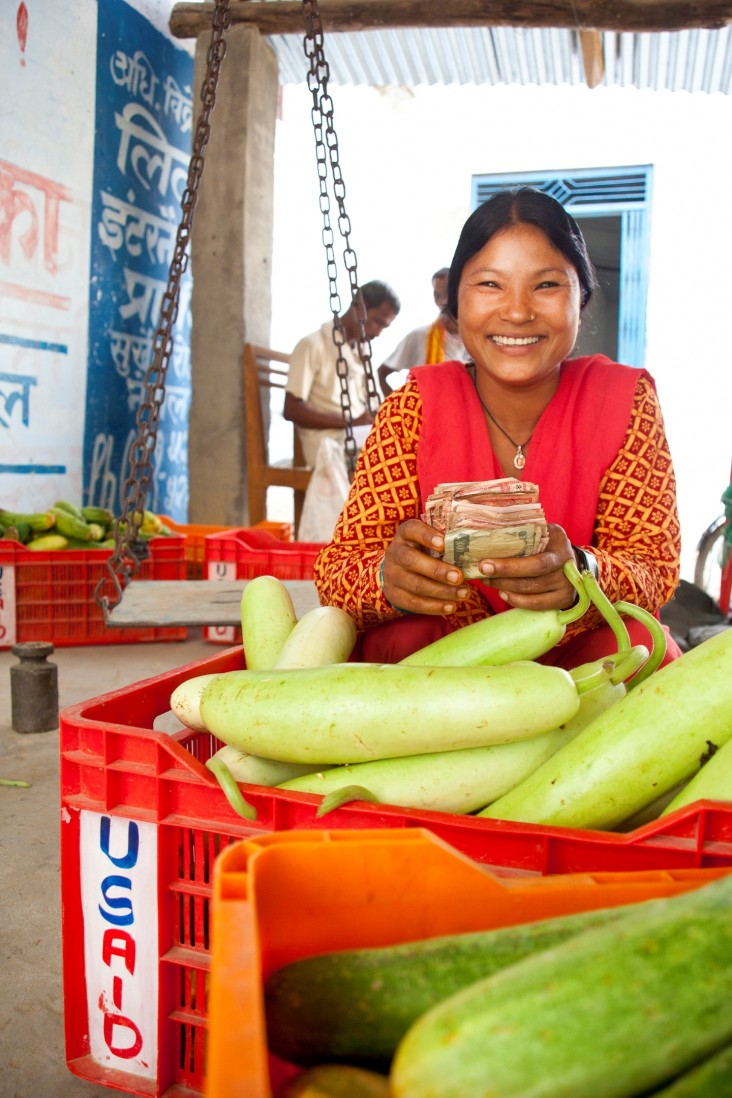 Ram Kumari Tharu displays her harvest and smiles after collecting her money from a local trader.