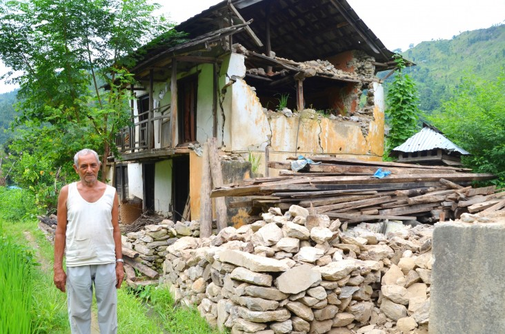 Farmer Rohini Prasad Kadariya, 74, stands next to his house in Ramechhap district destroyed by the first Nepal earthquake.