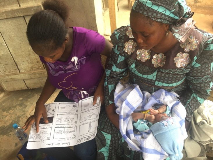 Two young mothers learn how to use chlorhexidine gel with a graphic chart.