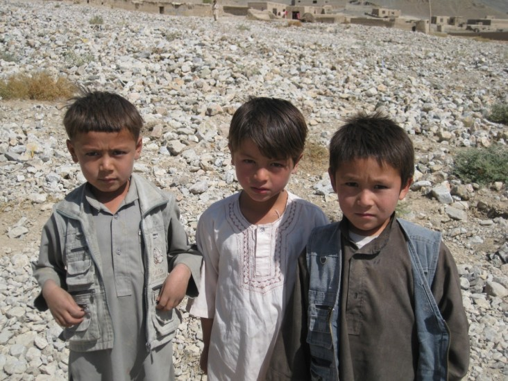 Three Afghan children looking at the camera