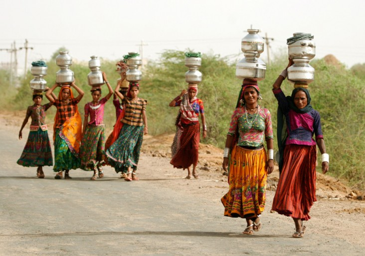 Working Together: Women carry jugs of water in India