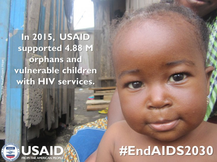 A baby looks at the camera. In 2015, USAID supported 4.88M orphans and vulnerable children with HIV services.