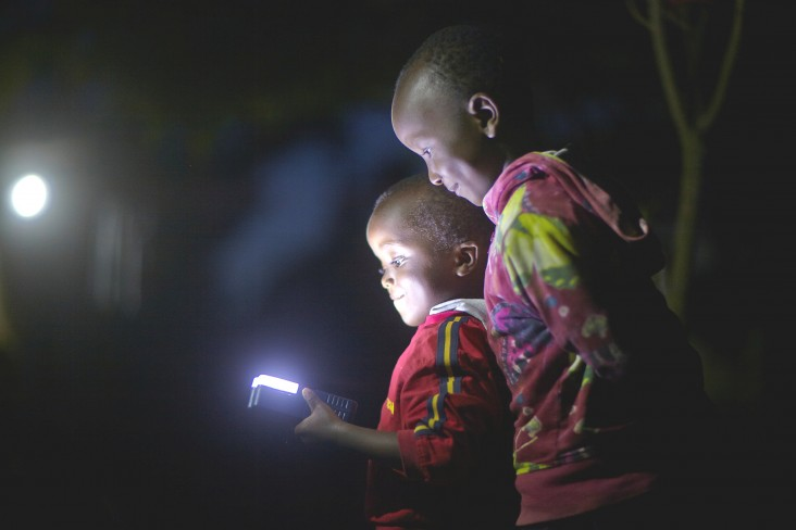 Children use a light powered by Off-Grid:Electric's solar service, mPower.