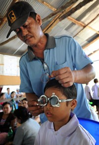 An young boy tries on different lenses with an optometrist.