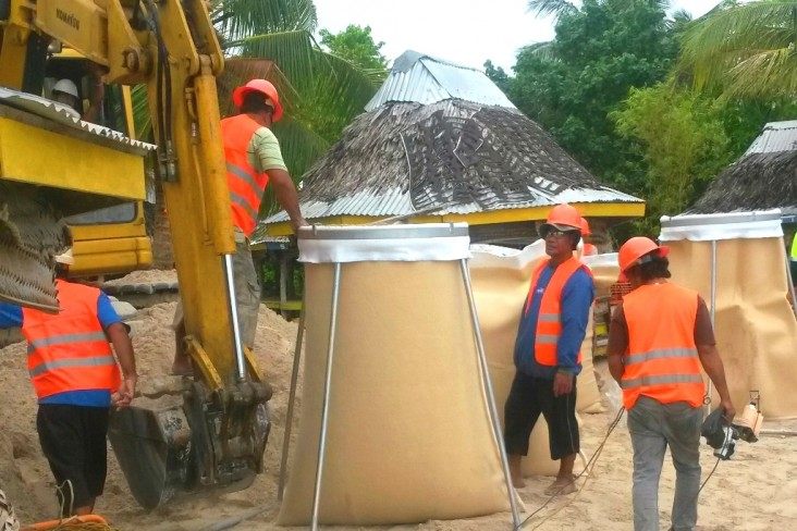 To quickly stop the erosion, workers filled geotextile bags with sand to place along the Manase coastline.