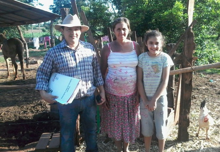 Dairy farmer Bernarda Gonzalez, center, with her daughter and a program specialist after a monitoring visit