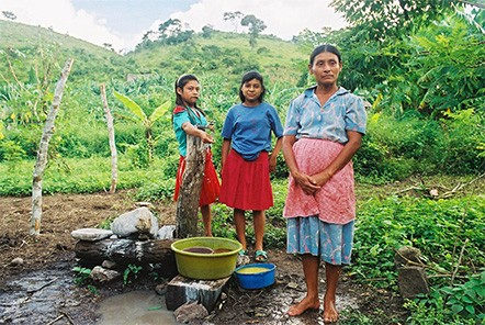 A Mayan-Chortí woman and her daughters collect water at a standpipe in a village near Copan Ruinas, Honduras.